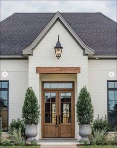Home Exterior Ideas 'Fixer Upper' Joanna Gains Reveals New Classic Style Home, modern farmhouse exterior with white painted brick and wood front door, double front door and farmhouse exterior lights and front porch decor with planters Design Exterior, Exterior Paint Colors, Exterior House Colors, Paint Colors For Home, Paint Colours, Fixer Upper Paint Colors, Fixer Upper Decor, Home Styles Exterior, Casas Shabby Chic