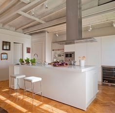 Cocina blanca con isla central y taburetes con asientos acolchados
