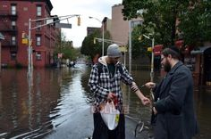This image depicts Rabbi Moshe Shapiro, whose Chabad House was destroyed by Hurricane Sandy, wrapping tefillin on another victim of the storm.