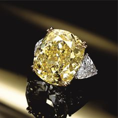 FANCY INTENSE YELLOW DIAMOND RING, VAN CLEEF & ARPELS, PARIS The cushion-shaped diamond of fancy intense yellow color weighing 33.45 carats, flanked by 2 triangular-shaped diamonds together weighing approximately 5.00 carats, mounted in platinum and 18 karat gold, size 6, signed Van Cleef & Arpels, numbered M41076, assay marks. With signed box.