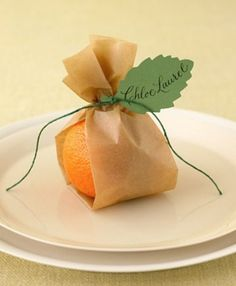 Mini oranges tucked inside strips of folded parchment paper bring warm color to the reception table; they're also a nice palate cleanser between courses. Instead with pears as escort cards? Place Settings, Table Settings, Faire Part Invitation, Wrapping Gift, Thanksgiving Place Cards, Christmas Place Cards, Thanksgiving Ideas, Wedding Party Favors, Fruit Wedding