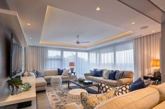 This modern living room has floor-to-ceiling windows in the corner along with a recessed ceiling with hidden lighting makes this already light room brighter. Decorated in blues, yellows, and grey, the living room brings tones of the beach from outside to inside.