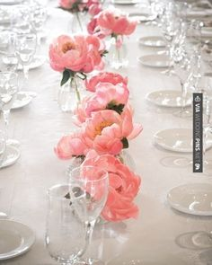 Clear bud vases at varied heights with coral peonies will line the back of the guest book table.