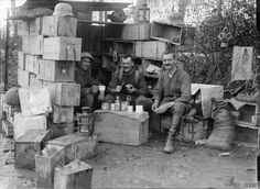 Three military policemen taking a meal whilst seated in a shelter constructed from ammunition boxes, at a prisoner of war transit camp at Saint Jean on 5th October 1917 after processing a batch of German prisoners who had been captured at Poelcapelle by the 11th Division of the British Fifth Army during the Battle of Broodseinde.
