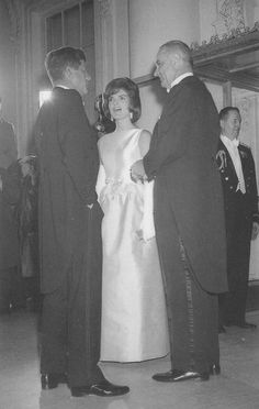 Jackie chats with JFK and Vice President Lyndon Johnson while waiting for the Shah and Empress of Iran to arrive for dinner. Jackie's sleeveless dress had a white bodice and pink satin skirt. She accessorized with long white gloves.