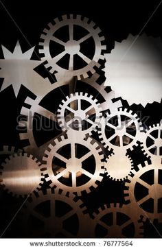 An artistic abstract closeup of mechanical gear wheels interlocking against black background for textural background. by Gwoeii, via ShutterStock