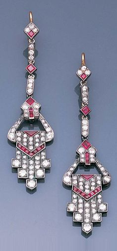 A pair of Art Deco ruby and diamond ear pendants circa 1930. The rhomb-shaped surmounts set with single-cut diamonds and a single calibré-cut ruby, suspending articulated links terminating in a geometric tapering drop set with old brilliant and single-cut diamonds, accented by a chevron of calibré-cut rubies, length 6.5cm.