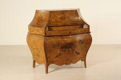 Ribalta in stile Barocchetto a doppia mossa su fronte e fianchi. Presenta quattro cassetti e anta con scarabattolo. Riserve in radica di noce.