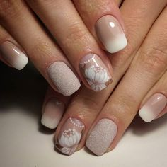 French manicure done by applying ombre technique and enriched with sticker of roses and sparkling sequins on ring finger's nail. Very classy.