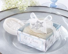 """Winter brings many joys to the season, especially the joy of snowfall! Our """"Let it Snow"""" Snowflake Soap Wedding Favors embrace the winter season and is a perfect favor or gift for any seasonal occasion. Features and facts:Round .8 oz white soap with a snowflake embossed in the centerSoap measures: 1.75"""" diameterSoap comes gift ready in an iridescent white gift box with printed gray snowflakes, clear pvc top,wrapped in a white organza ribbon and finished with a silver die-cut snowflake…"""