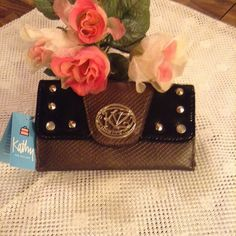 NWT Kathy Van Zeeland wallet New with tags, Kathy Van Zeeland wallet, brown trim in black with silver embellishments, front compartment has snap closure, front compartment has zipper compartment and pocket that you could store your $ bills in,  back compartment also has snap closure, back compartment has two side panels for credit cards and ID, both side pockets expands for easy excess and has an extra pocket, $ bills can also be stored in these pockets. Kathy Van Zeeland Bags Wallets