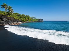 """With its jet-black shore, aquamarine waters and thick, jungle-like foliage, Honokalani Beach in Hana is a photographer's dream. Besides lying lazily on the """"sand""""—actually made up of of tiny lava pebbles—there's plenty to do: you'll find seaside lava tubes and sea caves carved into the lava cliffs along the shore. It's wild, unspoiled Hawaii at its best, and a necessary stop en route to Hana."""