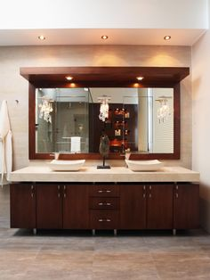 The large wooden vanity features double vessel sinks, cabinet and drawer storage, and an overhang with extra lighting. The large mirror reflects the glass shower with rainfall shower head and a beautiful wooden wall with cut-out shelves. The wood brings warmth to the room against the gray tile floor and light neutral walls.