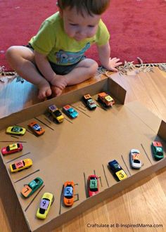 Toddler fun: number matchbox cars and build a parking lot out of a cardboard box. Number parking spots and kids match cars and spots.