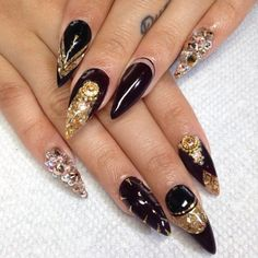 gold and black acrylic pointed design. i like the designs but i don't like the long or the pointed nails