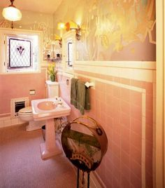 The pastel pink sink and matching tile have been in this 1925 Seattle bungalow since the beginning; the aquatic mural is recent. The tank on a stand is an antique fish aquarium. ♥ | Photo by Doug Keister | Arts & Crafts Homes #Vintage #ArtDeco #Pink