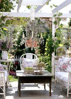 Amazing outdoor space with white wicker, soft floral prints...and a chandellier!
