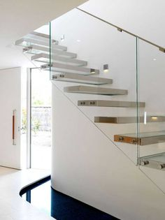 plexi stairs framed in metal, without risers, float in air against glass railing