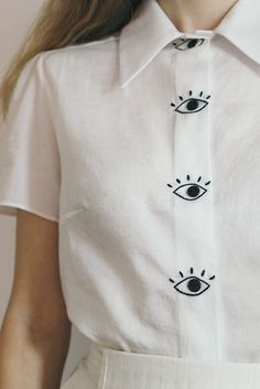 From the Tristan and Iseult collection. Cotton sateen blouse with hand-embroidered eyes and black buttons. The white option is made in a very light weight Japanese cotton satee Shirt Embroidery, Embroidery Fashion, Embroidery Designs, Diy Fashion, Fashion Outfits, Japanese Cotton, Japanese Embroidery, Embroidered Clothes, Diy Clothing