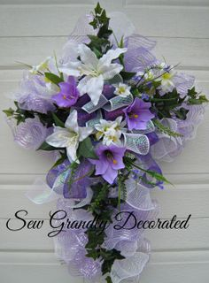 """""""He Is Risen"""".Honoring the true representation of Easter in designing this stunning Easter Cross Wreath. Full of lavender and white deco mesh 'ruffles', Easter Lily's, Ivy leaves and added florals and greens in white and purple. Church Flowers, Funeral Flowers, Wreath Crafts, Diy Wreath, Wreath Ideas, Easter Wreaths, Holiday Wreaths, Cemetery Flowers, Grave Flowers"""