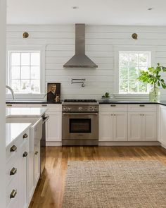 Black and white cottage kitchen features a white shaker cabinets paired with honed black countertops and a horizontal shiplap backsplash.