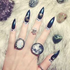 ..long blue stiletto nails with silver charms and moons and stars..