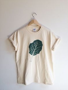 Hand Printed and Hand Drawn!  Show your love of greens with this 100% cotton screen printed t shirt. It features a large hand drawn kale leaf. It…