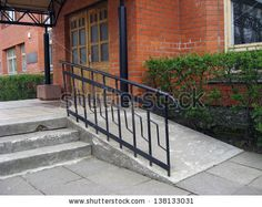 Building entrance with ramp for disabled person wheelchair by Grandpa, via ShutterStock