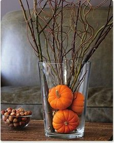 Rustic looking centerpiece with a vase filled with tiny pumpkins and branches.