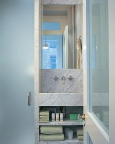 Small Wonder  Outfitting a tiny bathroom with just one material -- Carrara marble -- keeps it from feeling cramped or cluttered; a frosted glass door with a transom admits sunlight from the backyard.  (Love this Carrara marble - for everything)