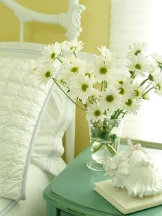 A distressed green bedside table supports a vase of fresh-cut daisies in this cottage-style bedroom. Soft white linens top the white iron bed next to the table, completing the bright, charming look of the space.