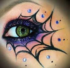 Purple and black spider web eye makeup with gems.