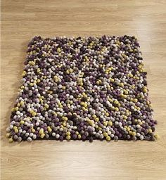 Pebble rug - I've been wanting to make a rug out of yarn pom poms but never thought about making them the color of pebbles.