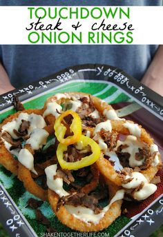 Touchdown Steak & Cheese Onion Rings are SERIOUS game day grub! Cover crispy onion rings in cheesy sauce with peppers & onions and top with seasoned beef!