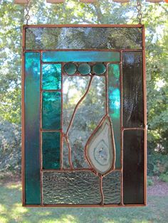 Cannon Beach #1 is approximately 7.0 inches x 10.5 inches and contains a polished teal agate with a crystal center. Stained glass colors include