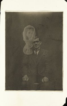 Joe Thomas and unidentified spirit  A photograph of the Welsh medium Joe Thomas, taken in about 1920. The shrouded woman's face appearing in the photograph was not identified by Thomas