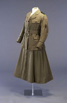 Image: Gently flaring mid-calf length skirt and jacket (worn together as a uniform) with long sleeves and four pockets, made of khaki twill-weave cotton. The uniform jacket fastens with 3 gold-coloured buttons: there is a same fabric belt which fastens using the middle of these three buttons. (picture: Mandy Reynolds)