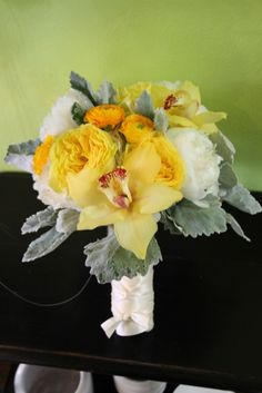Bridal bouquet of white hydrangea, peonies, yellow ranunculus, garden roses, and yellow cymbidium orchids by Beautiful Blooms by Jen.