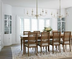 In this dining room, twin built-in breakfront cabinets flanking the bay window are graceful reminders of the home's heritage. | Photographer: Maxime Desbiens | Designer: Mélanie Cherrier