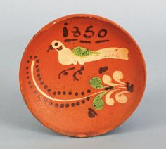 Sold   for   37,920.00  Pennsylvania redware pie plate dated 1850, above a green and yellow bird and floral sprig, 6 1/2 dia.