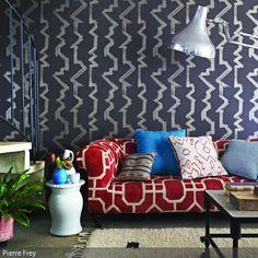 Die verschiedenen Muster der grauen Tapete, des roten Sofas und der Sofakissen gestalten einen zeitlosen Ethno-Look im Wohnzimmer. Das dunkle Grau ist im Gegensatz…