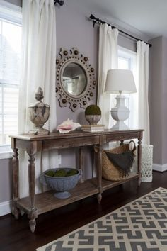 """""""This home doesn't have a foyer, so to fake one I placed a long console table on the wall,"""" says Jennifer. """"It also anchors the two windows, so they're not just floating there."""" The wood table offers a place for the homeowners to drop their keys and their dog's leash, but also adds warmth to the space. An impressive vintage mirror has unique detailing, but its taupe hue doesn't overwhelm. Console table, worldmarket.com"""