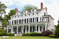 White clapboard house with black shutters, symmetrical chimneys, columned front porch, dormers -