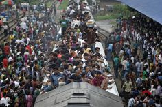 Passengers sit on the top of an overcrowded train as it approaches a railway station in Dhaka on Aug. 8. Millions of residents in Dhaka are traveling home from the capital city to celebrate the Muslim Eid al-Fitr holiday.