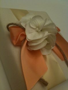 Premium wedding photo album with pale yellow ribbon, white hydrangeas, and a lush creamy peach bow!