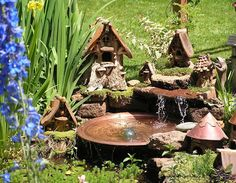 fairy garden with water feature! I wish there was a link to more pictures of this one, but someday, I will have a little pond with fairy houses tucked around it!