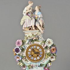Ornate Mantel Clock on Base  Meissen, swords underglaze blue, I choose, on a four-sided Rocaillesockel cambered case with figural finial in the form of a pastoral couple, brass dial with enameled roman numerals, percussion bell, rich plastic flowers lining, polychrome in gold, in addition to the watch case flower painting , clock model no. 573, base model no. 572, signs of age, remaining invisible., With Pendulum, Clock without base H 51 cm, total about 61 cm H, swords pommel end of 19…