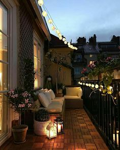 love this glowy look of moroccan lamps and globe string lights with puffy soft looking cushions on a balcony