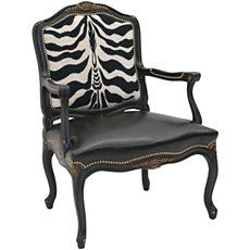 Create a striking statement in your room with this Zebra Print Carved Arm Chair by  Old Hickory Tannery . Featuring zebra print fabric on the inside of the chair back, recycled leather on the outside of the chair back, seat and arms. Accented with carved hardwood and nailhead trim, this dazzling chair makes a great accent piece for any room.