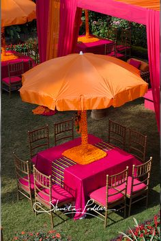 orange and hot fuschia pink decor, outdoor mehendi decor in farmhouse, table centerpieces as large umbrellas, kitsch, colorblocked, fun, funky, bright, fresh, vibrant mehendi decor drapes